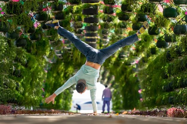Мужчина держит равновесие на одной руке в красочной арке с цветами и зонтиком на вокзале корниш. доха, катар. понятие о здоровье и силе.