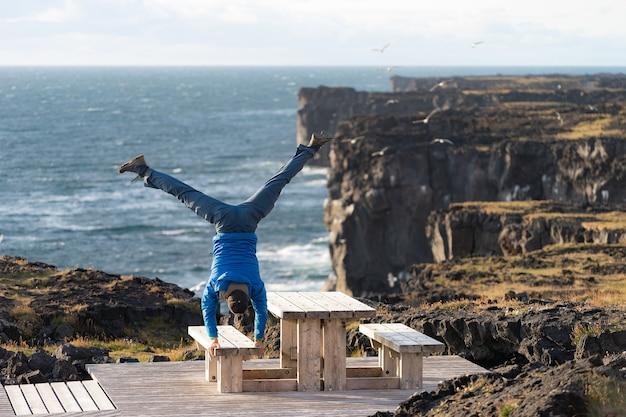 男は危険な垂直の崖の背景、日没時の雲景と海の風景に彼の手でバランスを保ちます