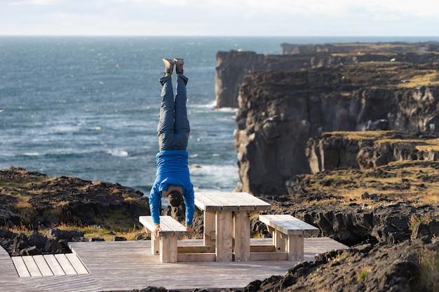 Человек держит равновесие, стоя на руках на морском пейзаже с опасной вертикальной скалой, облаками во время заката.