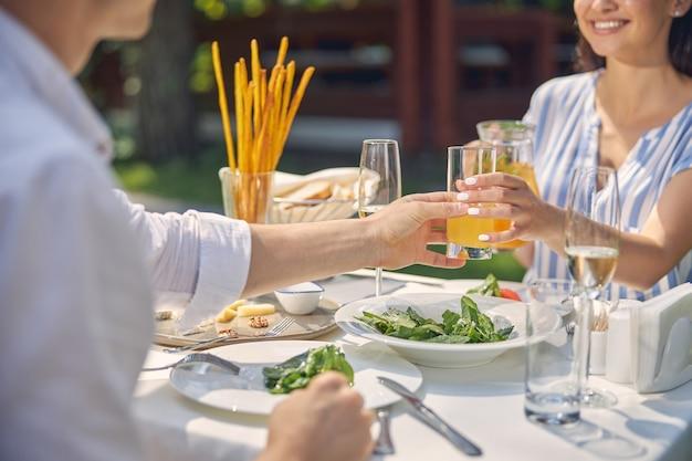 식탁에서 손에 오렌지 레모네이드와 유리를 유지하는 사람