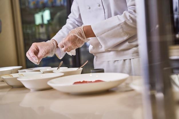 食べ物と一緒にいくつかの深い皿の上に手を保ち、皿にハーブとスパイスのピンチを投げる男