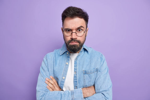 男は腕を組んで自信を持って表情を見せてくれる人の説明に耳を傾ける丸い眼鏡デニムシャツを着ている