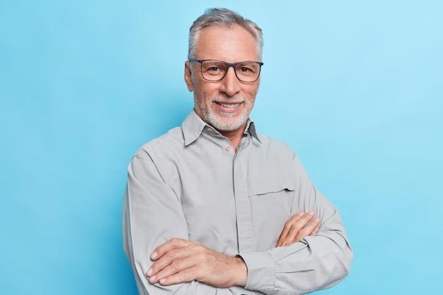 Мужчина держит руки, скрестив руки, смотрит с уверенным в себе веселым выражением лица, носит строгую рубашку и очки для коррекции зрения на синей стене