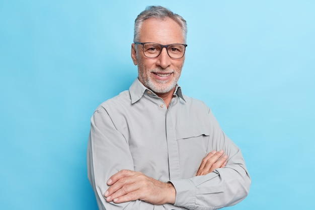 Man keeps arms folded looks with self confident cheerful expression wears formal shirt and spectacles for vision correction on blue wall