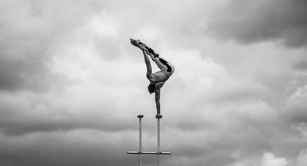Man keeps balance on one hand on the cloudy sky background. concept of yoga, meditation and healthy lifestyle.