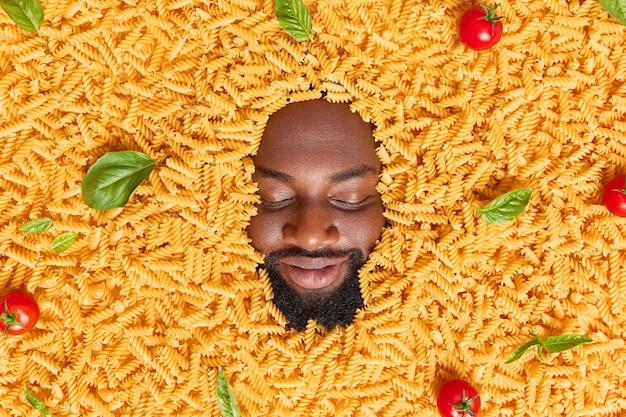 Мужчина держит глаза закрытыми с густой бородой, заросшей сырыми макаронами с красными помидорами и листьями базилика. ингредиенты для приготовления макаронных изделий. концепция питания и питания