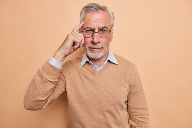 Man keeps finger on temple tries to recall something in mind focused at camera wears spectacles casual jumper isolated on brown