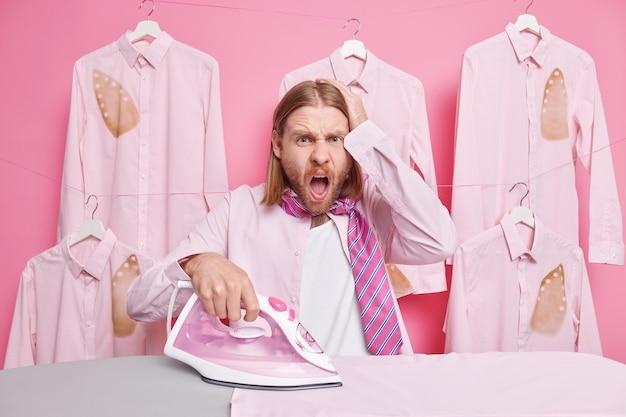 Мужчина держит руку на голове кричит отрицательно, будучи перегруженным работой по дому, гладит одежду с паровым утюгом позирует на розовом