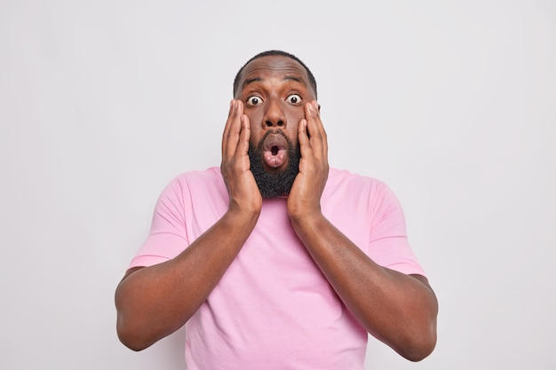 L'uomo tiene le mani sul viso reagisce a qualcosa di terrificante teso un'imboscata con le notizie indossa una maglietta casual
