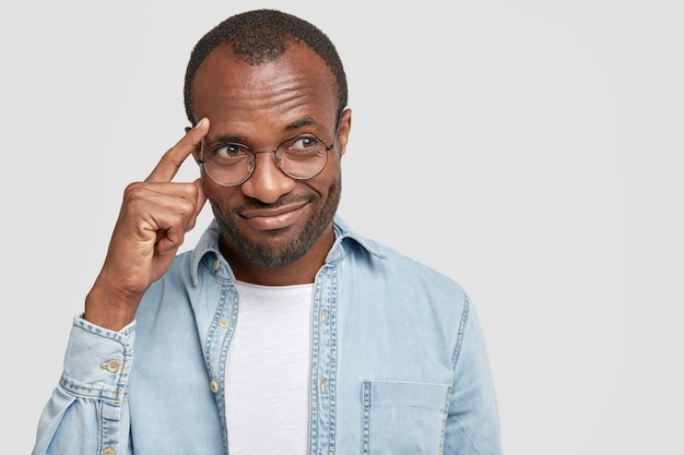 L'uomo tiene il dito indice sulle tempie, cerca di concentrarsi su qualcosa, vestito con una camicia di jeans, isolato su un muro bianco