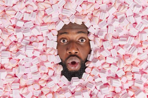 남자는 맛있는 마시멜로에 둘러싸여 입을 크게 벌리고 음식을 먹기를 기대하면서 맛있는 디저트를 먹는다