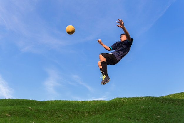 Man kick the ball at the stadium with blue sky