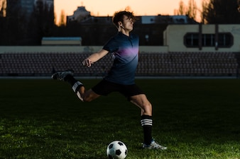 Man kicking ball with force