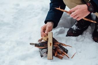Man kindle bonfire in winter snowy weather