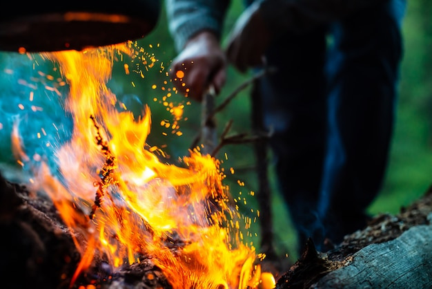Man kindles bonfire in forest. atmospheric flame of campfire close up. camping on nature. active rest. recreation open air. beautiful orange fire with smoke with copy space.