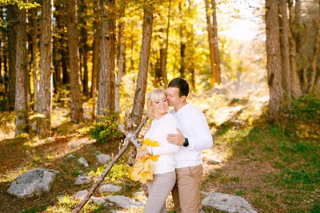 남자가 키스하고 웃는 여자를 어깨에 안아 여자가 그녀의 손에 노란 잎을 넓게 가지고 있습니다.
