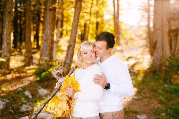 Man kisses smiling woman against an autumn forest, woman holding a bouquet