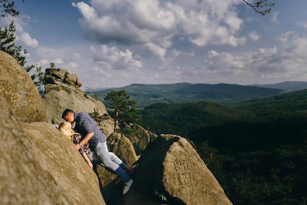 Man kisses woman standing before beautiful mountain landscape