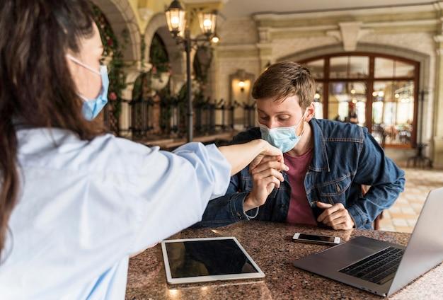 Мужчина целует руку женщины в медицинской маске