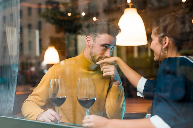 Man kissing hand of cheerful woman with glasses of wine in restaurant