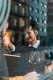 Man kissing hand of happy woman near glasses of wine and window of restaurant