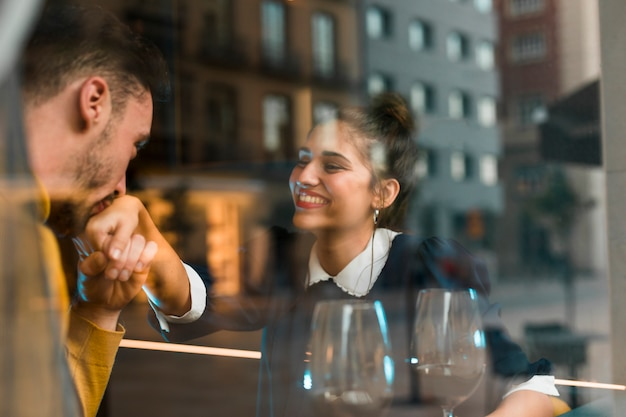 Man kissing hand of smiling woman near glasses of wine in restaurant near window