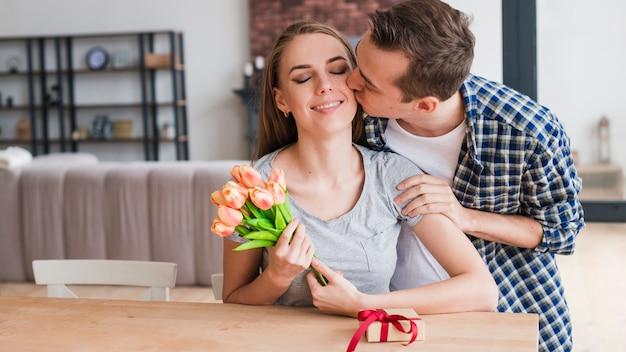 Мужчина целует счастливую жену и дарит подарки