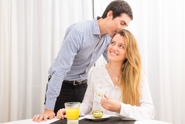 Man kissing her wife eating kiwi with spoon