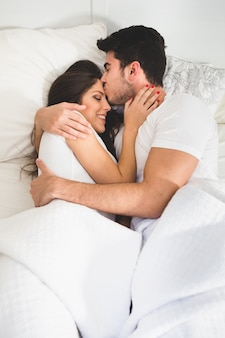 Man kissing his girlfriend on the forehead while lying on the bed