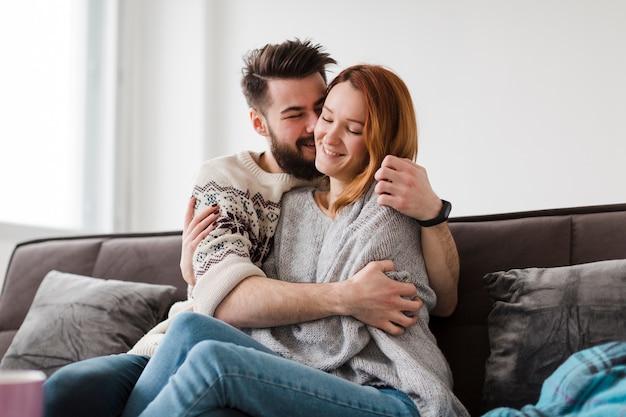 Мужчина целует свою подругу в гостиной