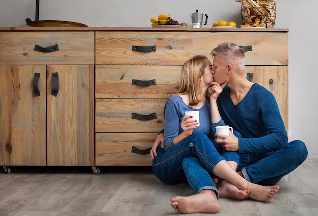 Мужчина целует свою подругу в щеку сидя на полу