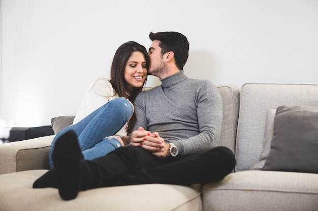 Man kissing his partner on a couch