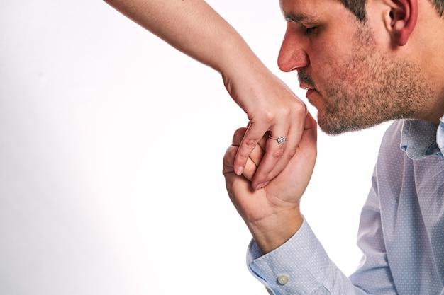 結婚指輪でパートナーの手にキスをする男バレンタインデーのコンセプト、恋に落ちたカップル、お互いに提案。