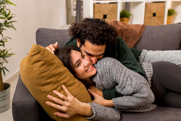 Man kissing his smiley wife while lying on the sofa