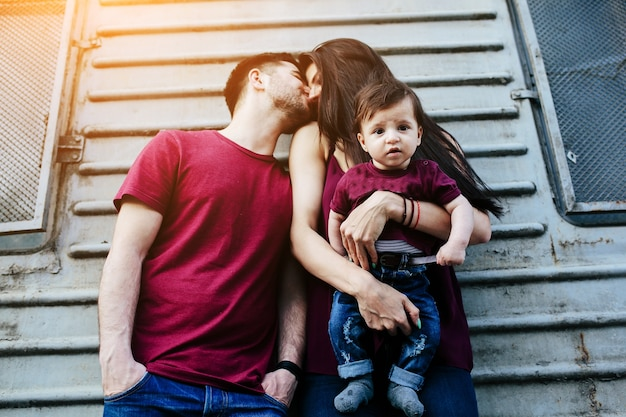 Man kissing his wife on the head and this one has the baby