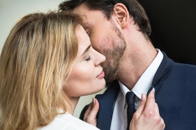Man kissing pretty blonde woman standing closed eyes in foreground