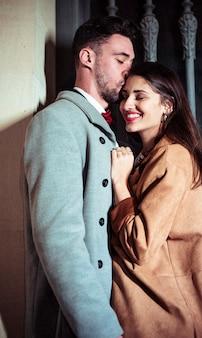 Man kissing pretty woman on forehead in street