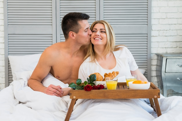 Man kissing smiling woman in bed near breakfast on board