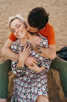 Uomo che bacia teneramente il collo della moglie abbracciandola con mani splendidamente tatuate mentre si rilassa sulla sabbia