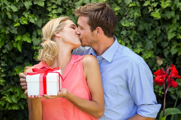 Man kissing while giving gift to woman at front yard