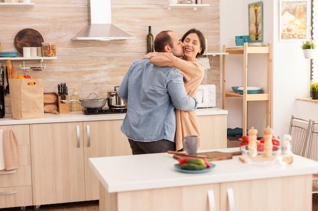 부엌에서 낭만적인 춤을 추는 동안 부엌에서 아내에게 키스하는 남자. 아내와 남편의 사랑, 로맨스, 부드러운 순간, 집에서의 재미와 행복, 공생 음악 쾌활하고 미소