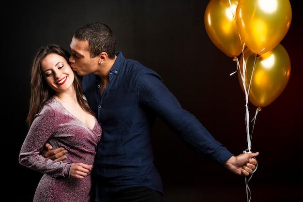 Мужчина целует женщину на новогодней вечеринке