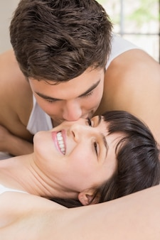 Man kissing woman on bed in bedroom