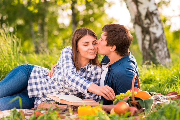 Man kissing woman on cheek in forest