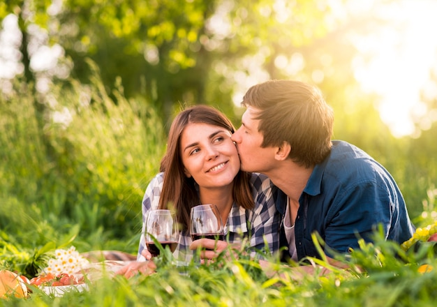 Man kissing woman on cheek on picnic