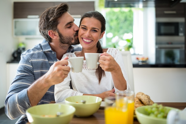Man kissing on woman cheeks while having breakfast