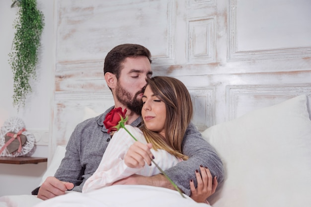 Man kissing woman on forehead in bed
