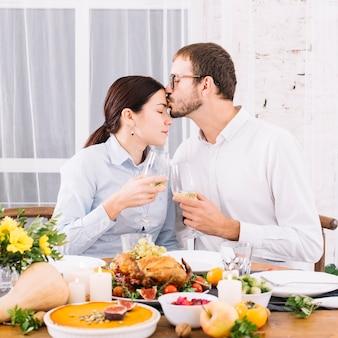 Man kissing woman at forehead