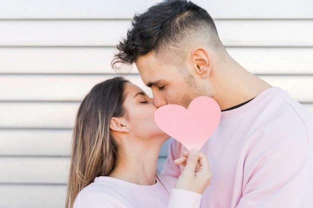 Man kissing woman holding decorative paper heart