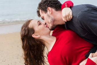 Man kissing woman holding her in arms